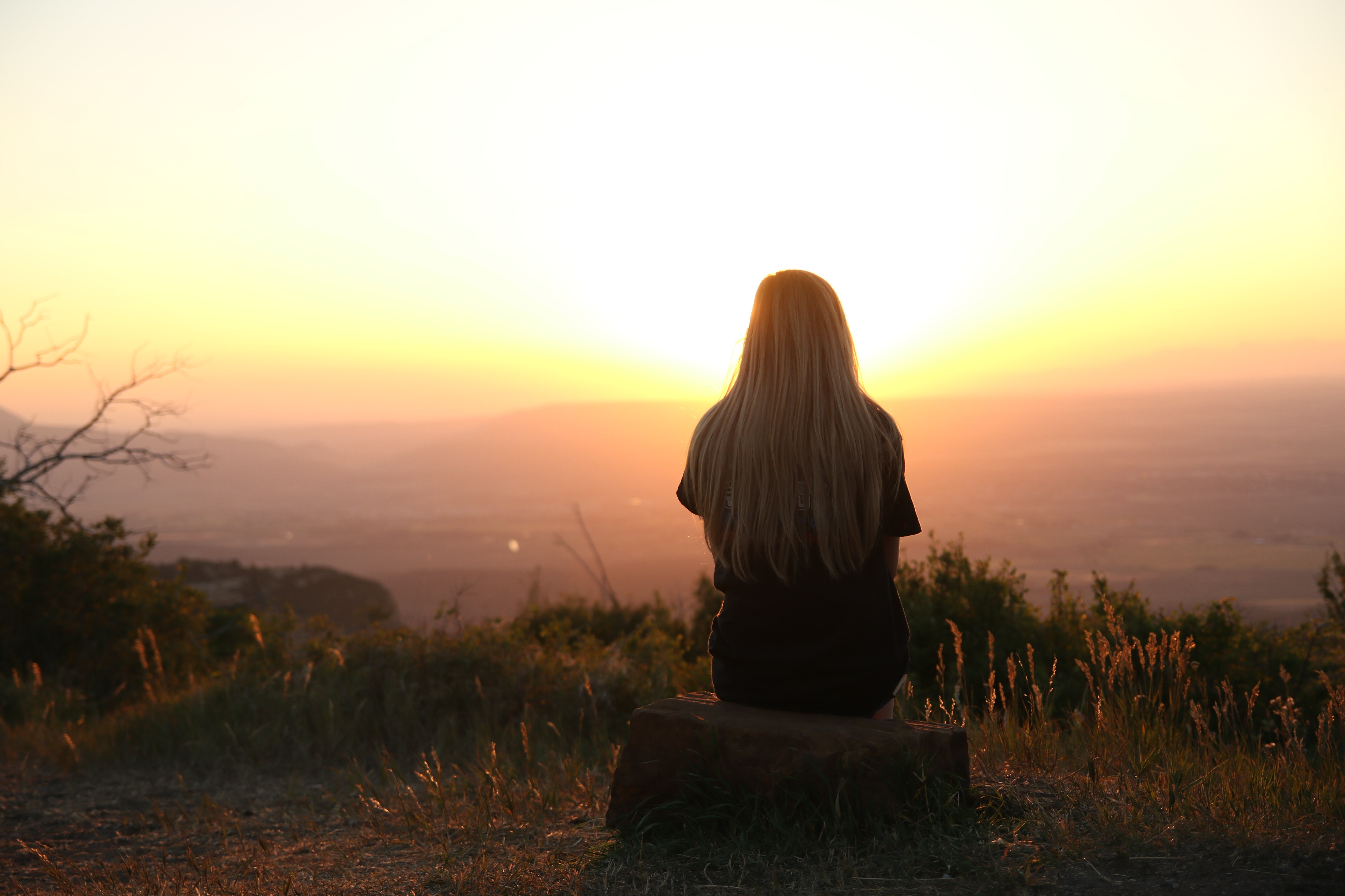 Girl sitting looking at sunset