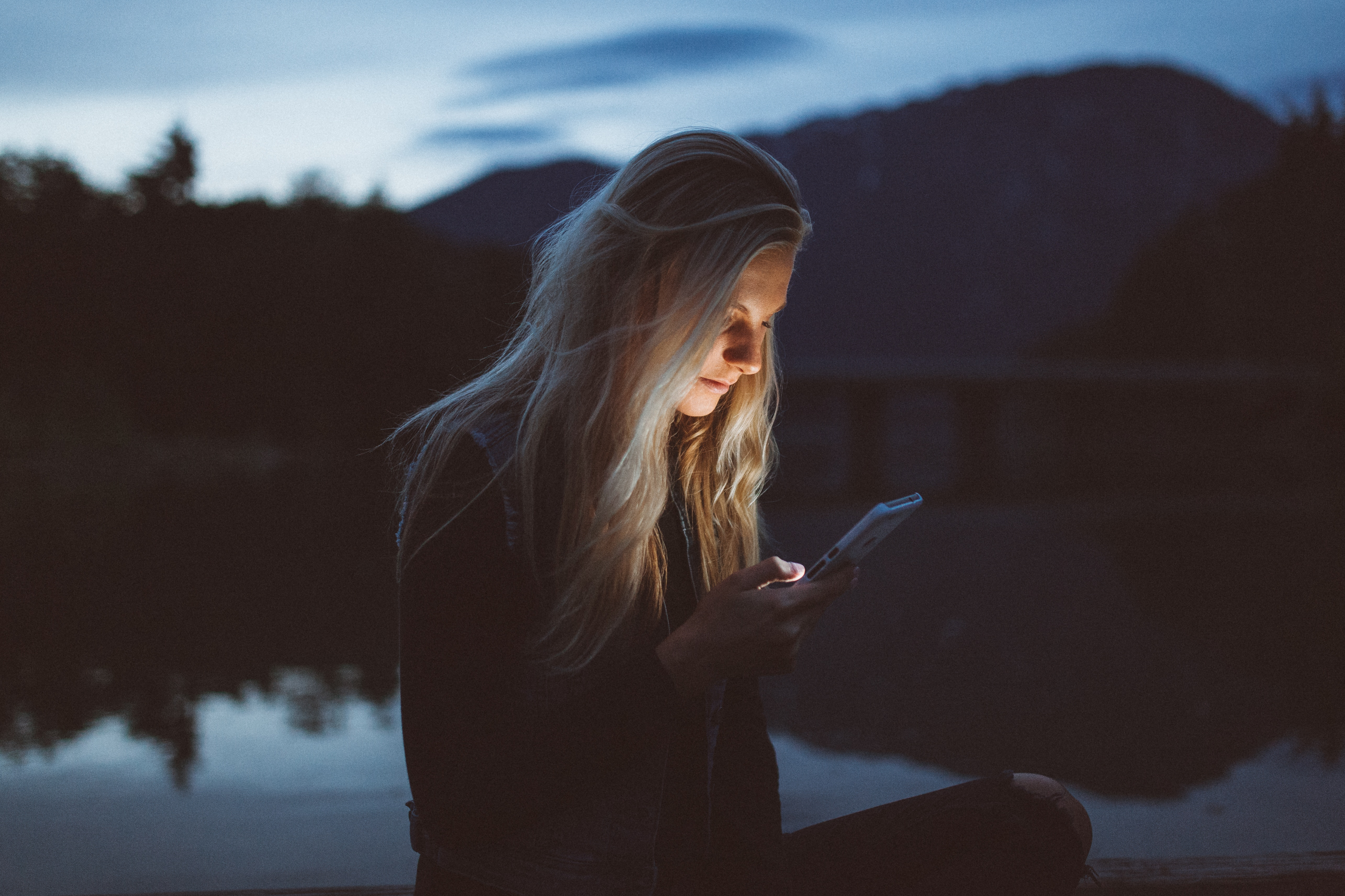 teen girl looking at phone in front of lake