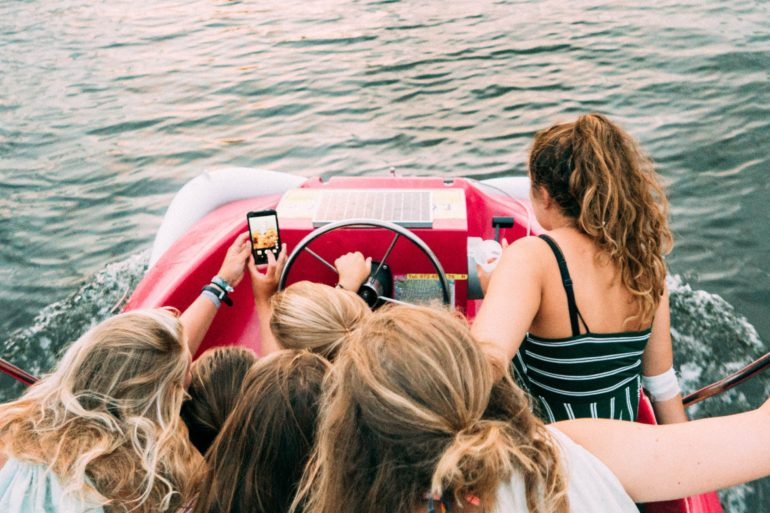 teen girls on boat taking a selfie together