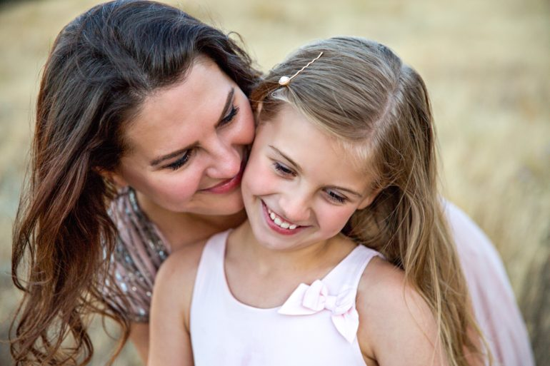 girl standing smiling with mom