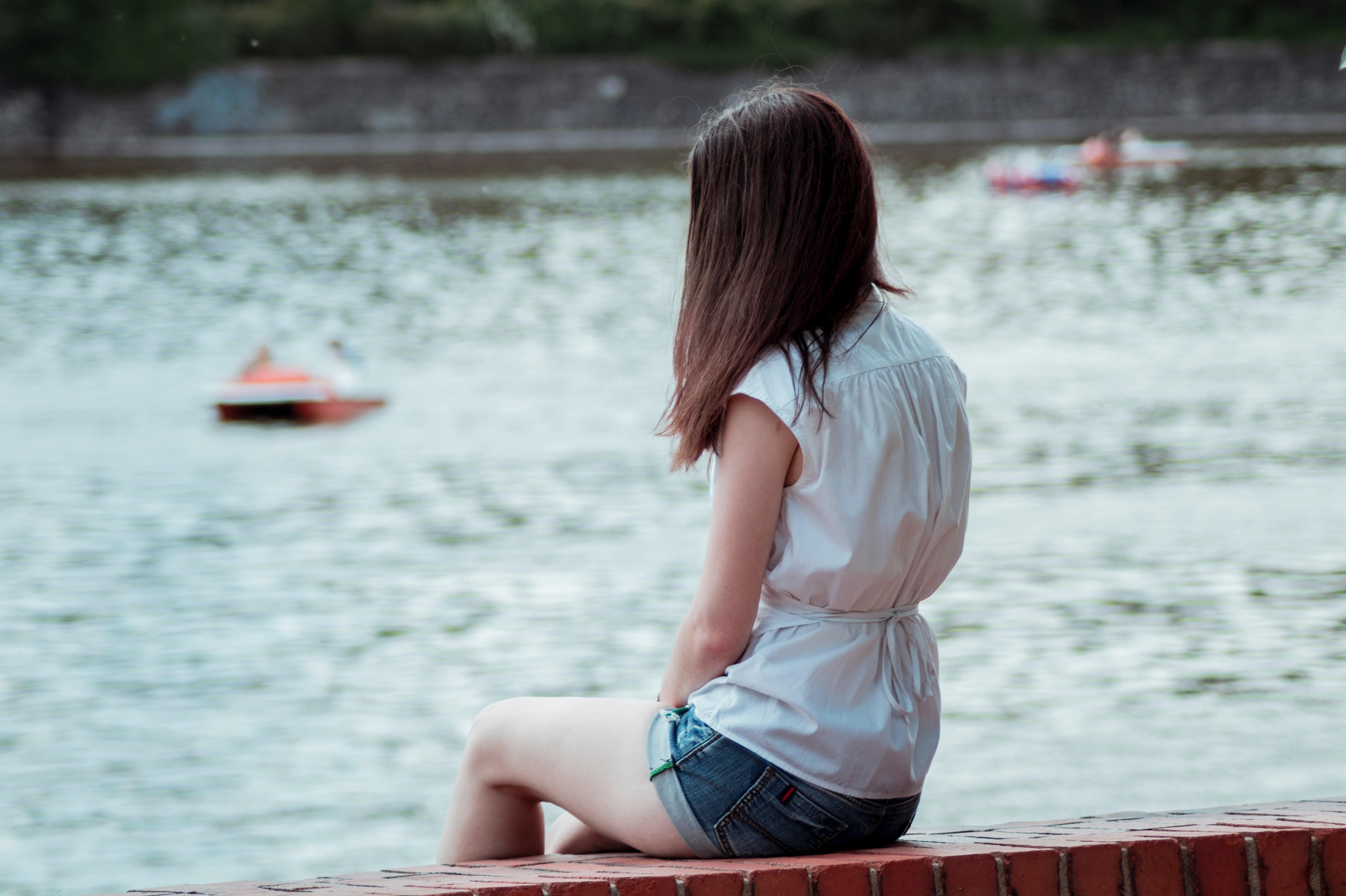 teen girl sitting on dock looking out at water