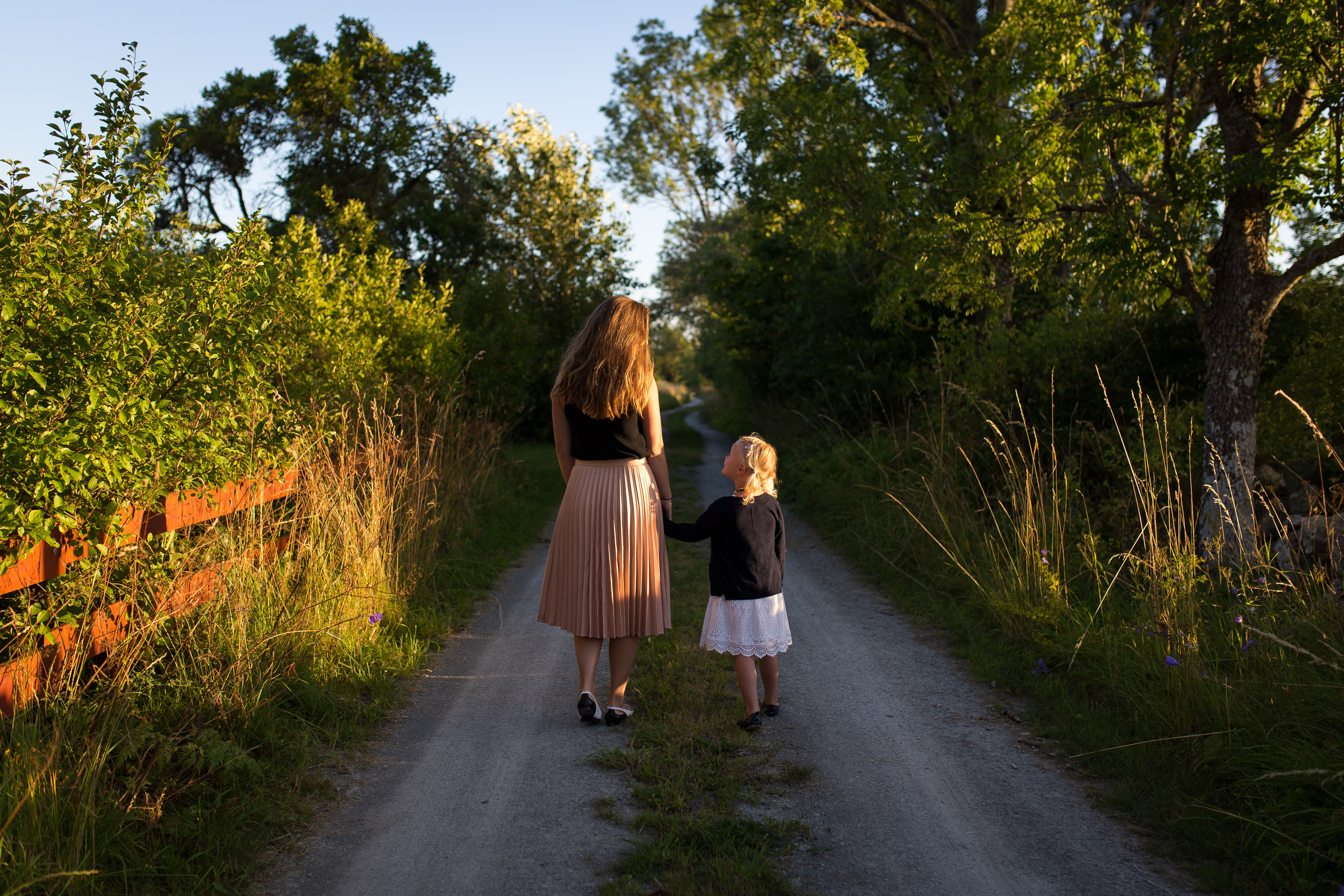 mother and daughter walking on gravel road surrounding by trees and brush