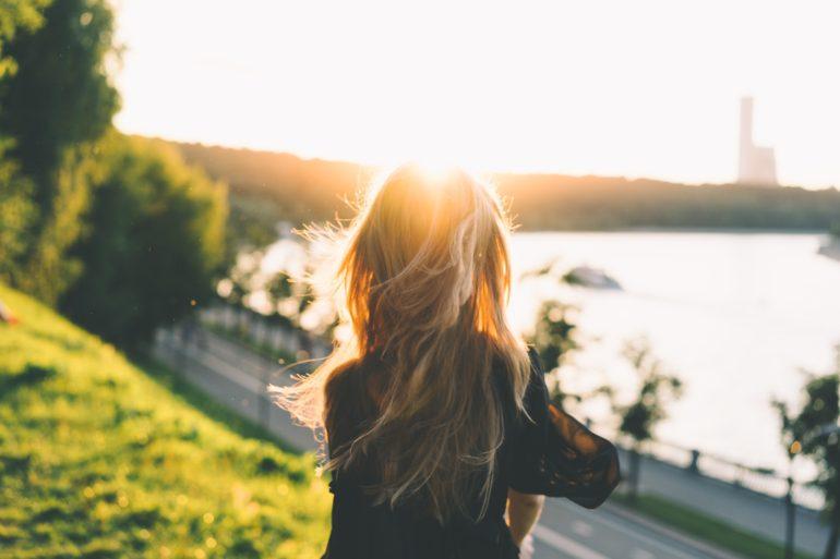 girl facing away looking at sunset