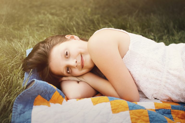 preteen girl lying on blanket in grass looking at camera