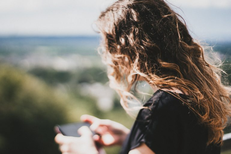 teen girl curly hair looking at phone in landscape